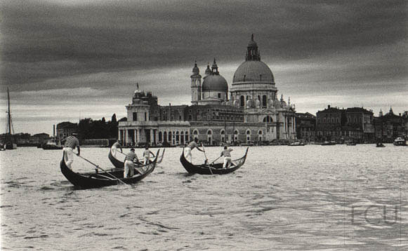 Black and white photo of Santa Maria della Salute on Grand Canal with gondoliers in Venice, Italy from vaporetto stop San Marco calle Vallaresso