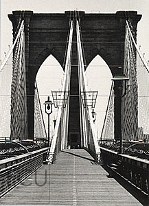 Black and white photo of the landmark Brooklyn Bridge and its stone arches and cables taken from the walkway in New York, New York