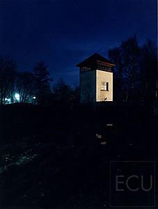Color photo of a guard tower taken at dusk at the Dachau concentration camp in Germany