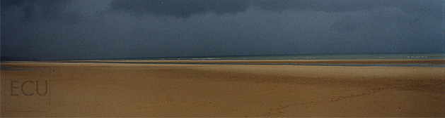 Color photo of Omaha Beach in Normandy France taken on Christmas Day under stormy winter clouds