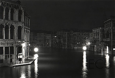 Black and white photo of the Grand Canal at night from the Ponte Rialto in winter in Venice, Italy