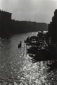 Black and white photo of the Grand Canal and gondolier from the Ponte Rialto in Venice, Italy
