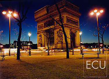 Color photo of the Arc de Triomph in Paris taken at dusk from the north side of Etoile in winter in France
