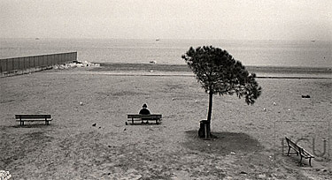 Black and white photo of a woman in winter on Lido Beach along the Adriatic Sea in Venice, Italy