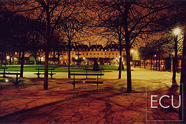 Color photo of the Place des Vosges on the Right Bank in Paris, France at night exemplifying landscape architecture of Henri IV