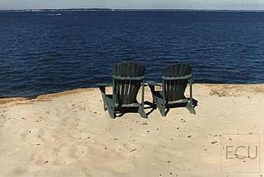 Color photo of chairs sitting atop of a beach escarpment overlooking Peconic Bay in Southampton, New York