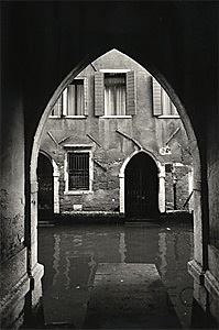 Black and white photo of the Calle de l'Aquila Nera which ends in an arch near Rialto reflecting the essential vernacular design of Venice, Italy
