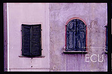 Color photo of a colorful wall and windows in the mountain village of Belluno in the Veneto, Italy