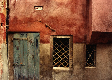 Color photograph of a painted Venetian door and wall with a fenced window