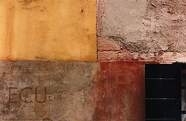 Color photograph of a modern, Venetian wall in yellow, red, black and brown