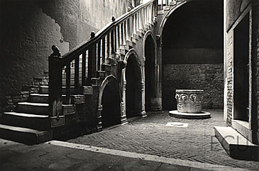 Black and white photo of the arch supported stairs in the Ca' Goldoni, home of the playwright Carlo Goldoni, in Venice, Italy
