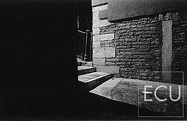 Black and white photo of an entrance to a Venetian bridge in Venice at night with space disappearing into darkness