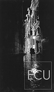 Black and white photo of a couple walking in the rain approaching Campo San Rocco at night in San Polo sestiere of Venice, Italy