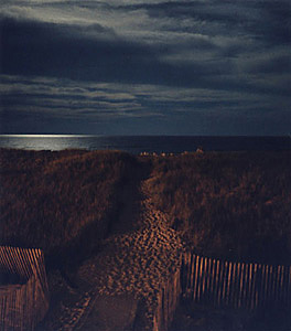 Color photo of Westhampton Beach taken at night on the ocean with a full moon